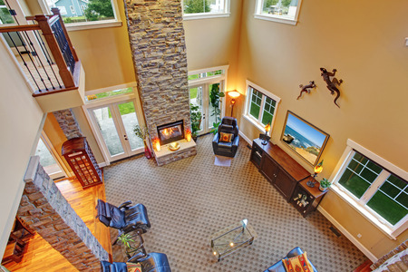upstairs: Luxury living room with high ceiling, brick columns and fireplace. View from upstairs deck
