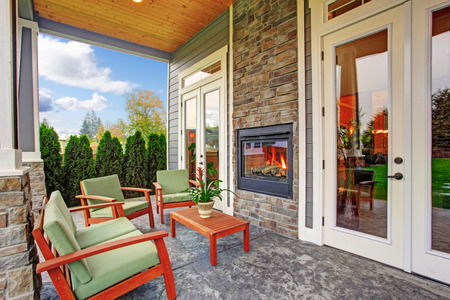 Cozy backyard deck with wooden furniture set and built in the wall fireplace photo