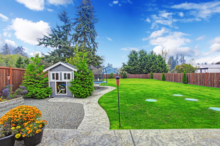 fenced: Fenced backyard with lawn, concrete walkways and small wooden shed