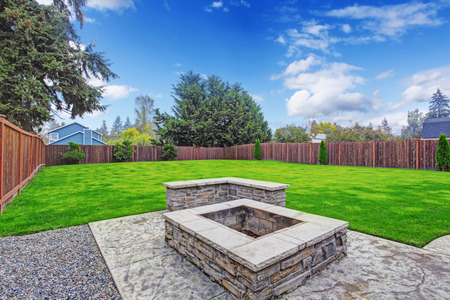 Fenced backyard with lawn and firepit on concrete base