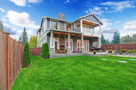 Luxury house with backyard walkout deck and column porch. View of lawn with trees and flower pots photo