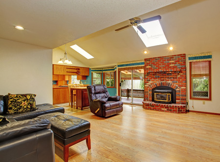 Ivory house interior. View of living room with brick background fireplace, leather furniture set and kitchen area photo