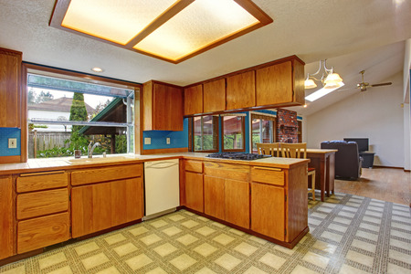 Bright kitchen room with skylight and linoleum. View of dining and living room photo