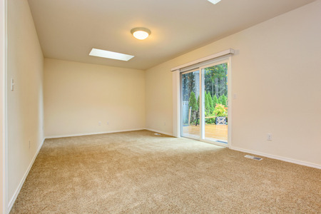 slide glass: Bright soft ivory empty room with beige carpet floor and slide glass door to walkout deck