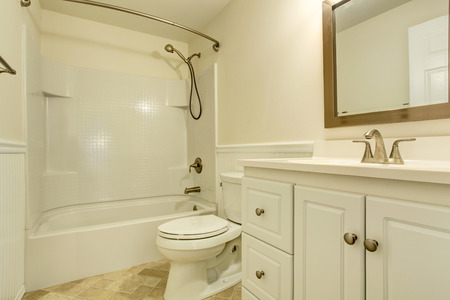 bathtub: Empty white bathroom with white vanity cabinet and mirror