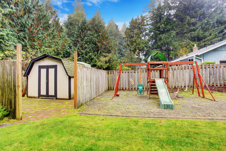 Backyard with small shed and playground for kids photo