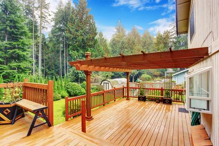 Amplia terraza de madera con bancos y pérgola adjunta.