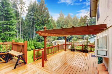 Spacious wooden deck with benches and attached pergola Stok Fotoğraf