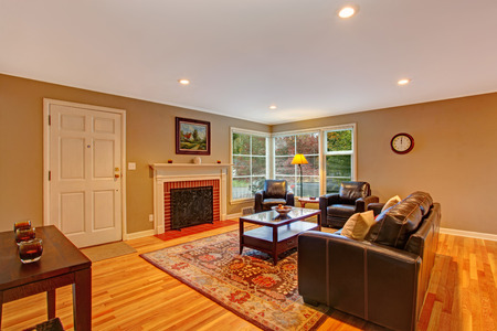 Classic living room interior with fireplace, hardwood floor with rug and leather furniture set photo