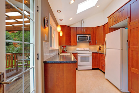 skylights: Bright kitchen room with vaulted ceiling and skylight. White appliances refresh the interior.