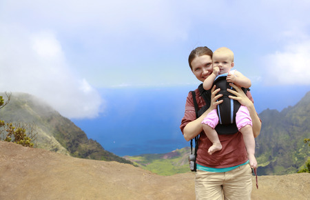 six months: Mother is holding her six months baby in a carrier in Kauai. Hawaiian islands