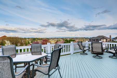 Spacious walkout deck with railings. View of patio area with table set and fire pit photo
