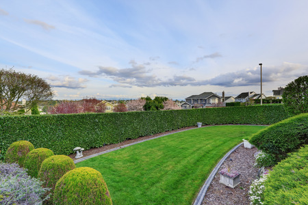 hedged: Beautiful front yard landscape with trimmed hedged and green lawn