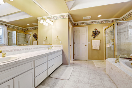 Spaciou luxury bathroom interior with white tile floor, white bathroom vanity cabinet, glass door shower and bath tub photo