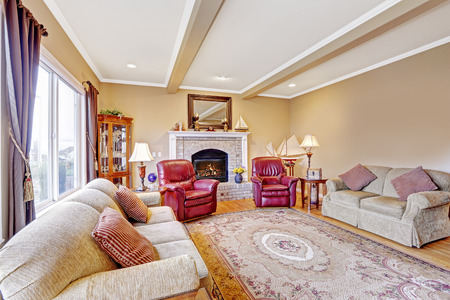 view of an elegant red couch: Luxury living room interior with brick background fireplace, hardwood floor and rug. Furnished with comfortable sofa and leather armchairs Stock Photo