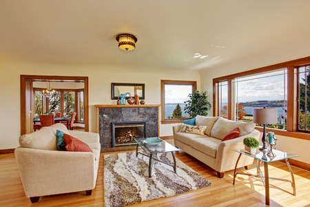 Living room interior with ivory furniture set , soft rug on hardwood floor and cozy fireplace