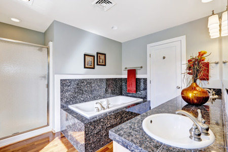 bathroom interior: Modern bathroom interior with black granite tile trim and white bath tub and sink Stock Photo