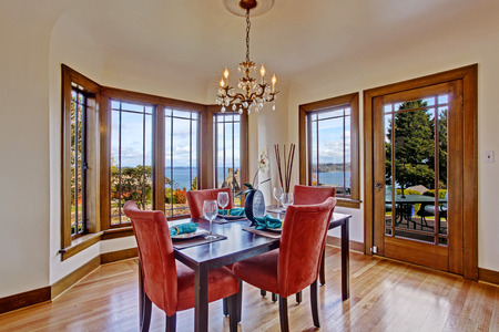 designer chair: Luxurry dining room with hardwood foor and walkout deck. View of black and red dining table set with served table