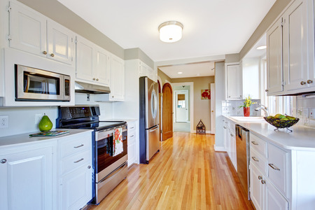 appliances: Kitchen room with hardwood floor, white storage combination and steel appliances