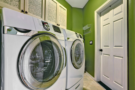Small birhgt green laundry room interior with white modern appliances Banque d'images