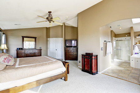 master bedroom: Luxury bright master bedroom interior with bathroom. View of bed with bedroom vanity cabinet, tv and dresser