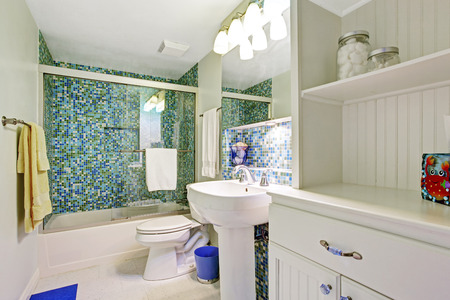 white trim: Refreshing white bathroom with aqua tile wall trim, whtie wooden cabinet, washbasin stand and toilet