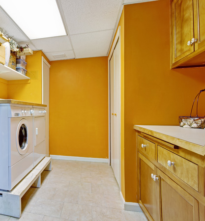 Bright yellow laundry room with white appliances photo