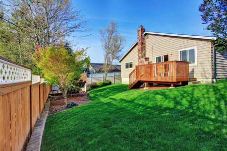 fenced: Small fenced backyard with wooden walkout deck