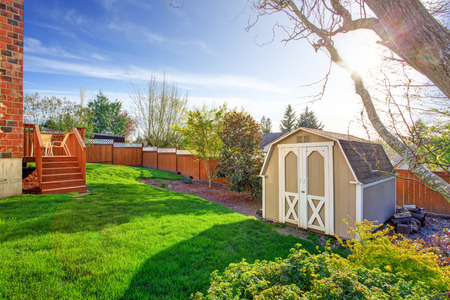 Fenced backyard with wooden walkout deck and small shed photo