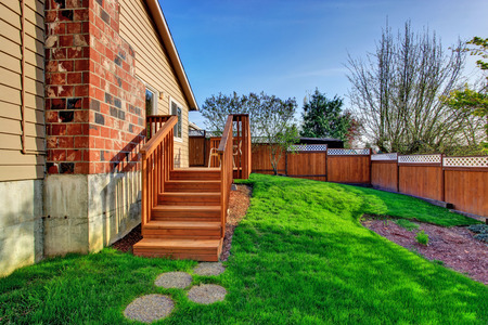 fenced: Fenced backyard with wooden walkout deck Stock Photo
