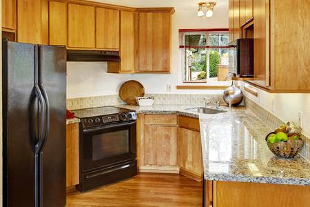 black appliances: Bright small kitchen room interior with black appliances