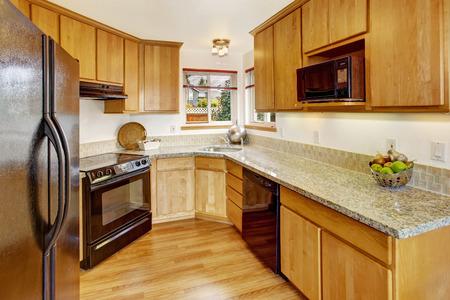 black appliances: Luminoso interior piccola camera cucina con elettrodomestici neri