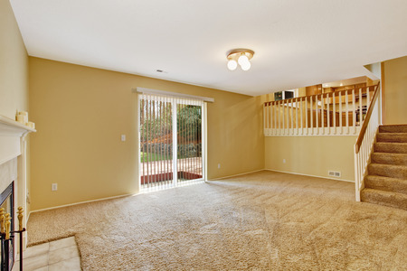 remodeled: Empty house interior. View of empty living room with walkout deck and staircase to kitchen