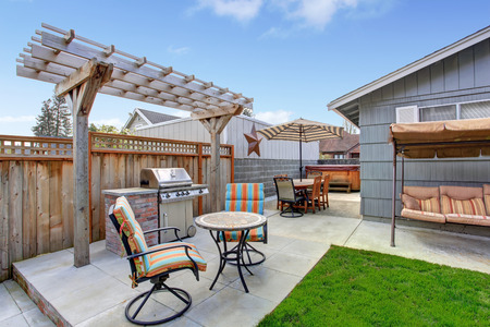 House backyard with juacuzzi, small patio area and garden swing photo