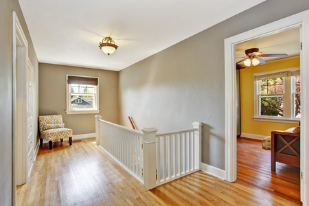 upstairs: Empty upstairs hallway with hardwood floor and white staircase. Decorated with yellow chair in the corner