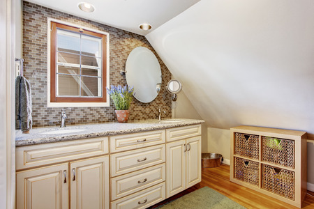 vanity: Velux bathroom with tile wall trim. View of bathroom vanity cabinet and storage unit with wicker baskets