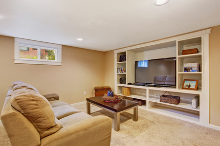 Cozy room in soft brown color with comfortable sofa, coffee table and tv photo