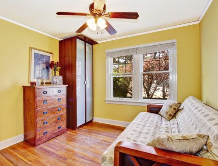 bedroom furniture: Bright yellow small room with walk-in closet. Furnished with sofa, wardrobe and dresser