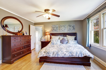 Master bedroom interior in light grey color. View of queen size bed and dresser photo