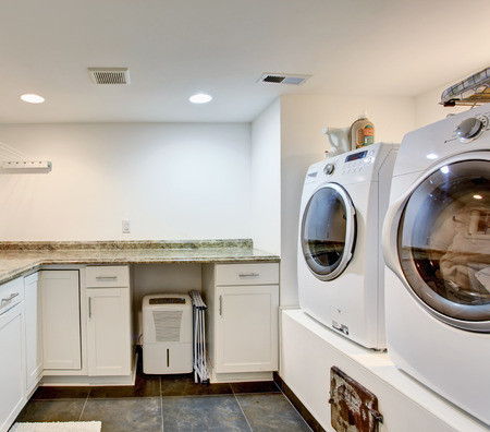 Laundry room with storage cabinets and modern appliances