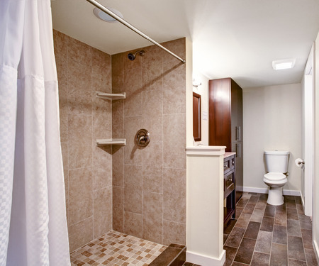 bathroom wall: White bathroom with mocha tile wall trim and tile floor. View of shower with white curtains Stock Photo