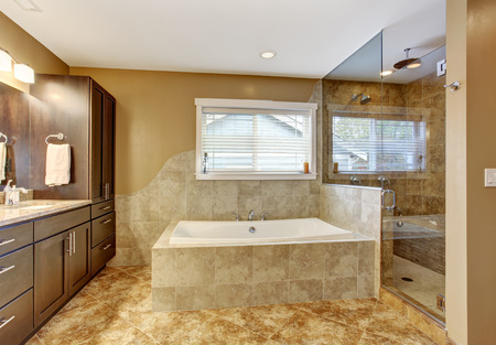 bathroom tile: Modern bathroom interior with tile wall trim and tile floor. View of white bath tub, brown storage combination and glass door shower