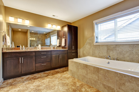 Modern bathroom interior with tile wall trim and tile floor. View of white bath tub and brown storage combination photo