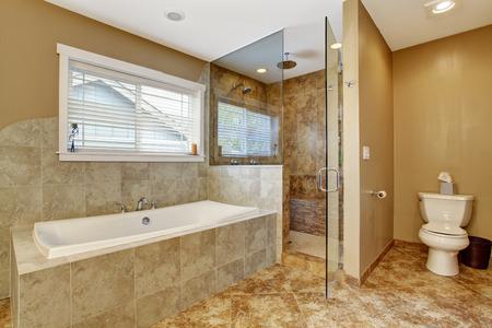 Moderno cuarto de baño interior con tapicería de la pared del azulejo y piso de baldosas. Vista de la tina de baño blanca y ducha con puerta de vidrio