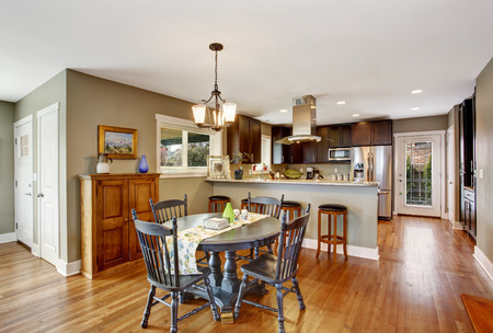 Dark brown kitchen room with round rustic dining table with chairs Stock Photo