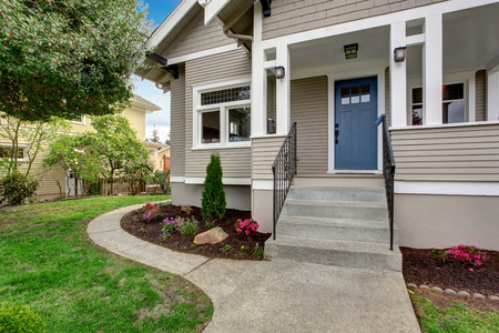 House exterior with entrance porch. View of staircase and front yard landscape Standard-Bild