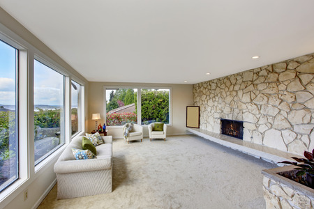 Bright living room with rock wall trim in luxury house. Furnished with white couch with chairs. photo