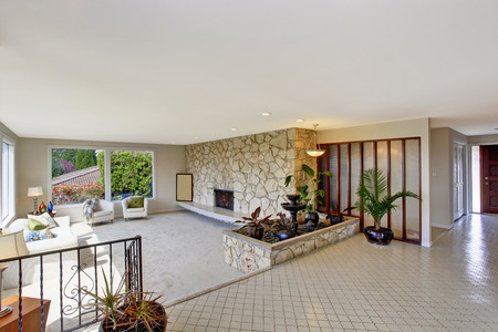 Bright living room with fountain in luxury house. View of entrance hall with tile floor photo