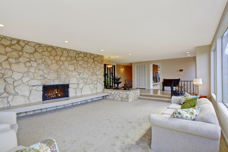 Bright living room with fountain in luxury house. View of fireplace built-in in rock wall photo
