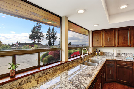 Kitchen room with dark brown cabinets and granite counter top. photo